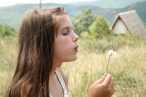 girl-blowing-dandelion